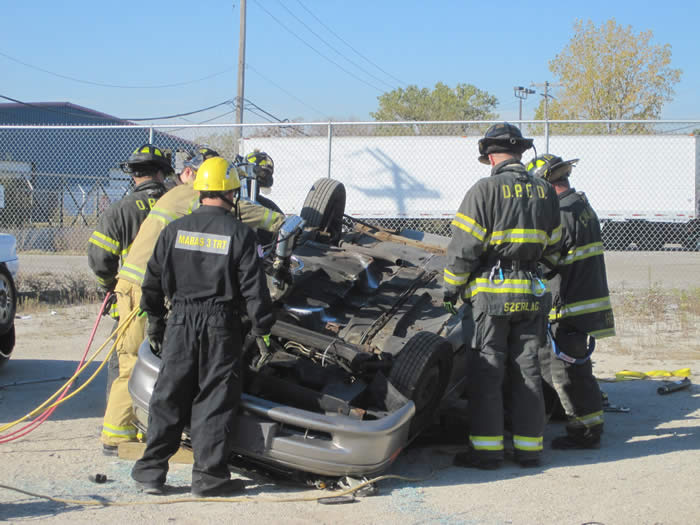 Firefights standing around overturned car