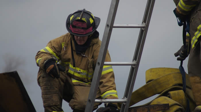 Firefighter crouched near ladder