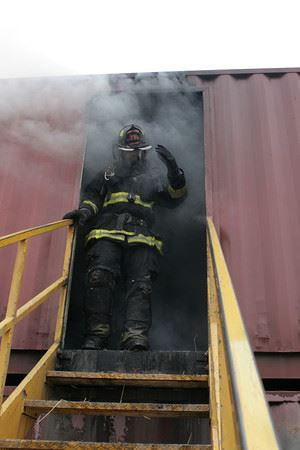 Firefighter coming out of smoking building