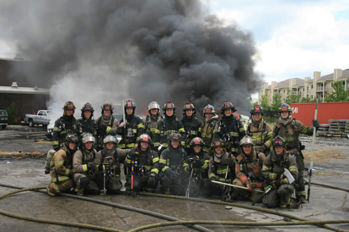 Firefighters posing for photo in front of fire