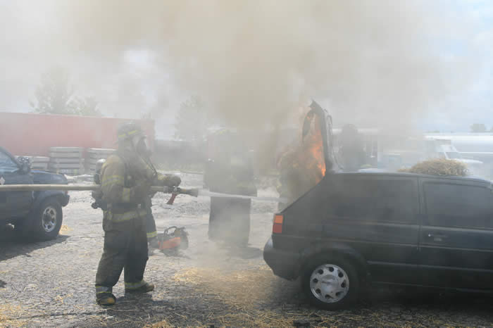Firefighter spraying car with hose