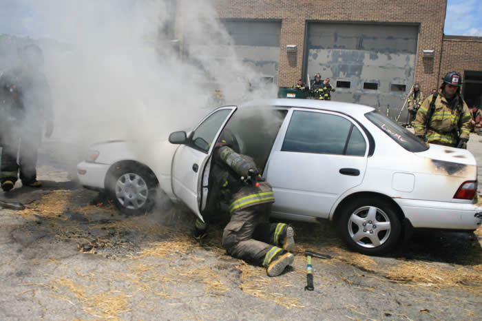 Firefighter in car with smoke coming out of it
