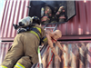 Firefighter removing mannequin from burning building