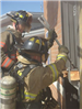 Firefighter opening window with halligan