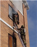 Firefighter climbing into building from ladder
