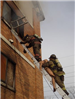 FIrefighters climbing down ladder with mannequin
